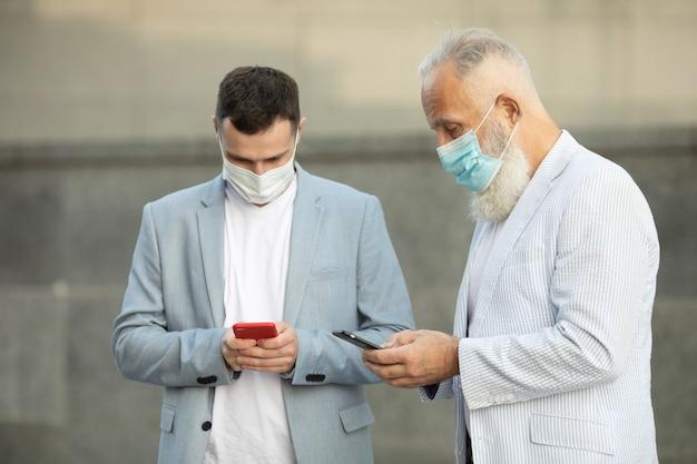 Twee zakenlieden in beschermend masker buiten kantoorgebouw bespreken