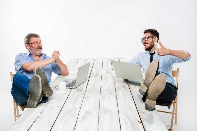 Twee zakenlieden met benen over tafel werken op laptops