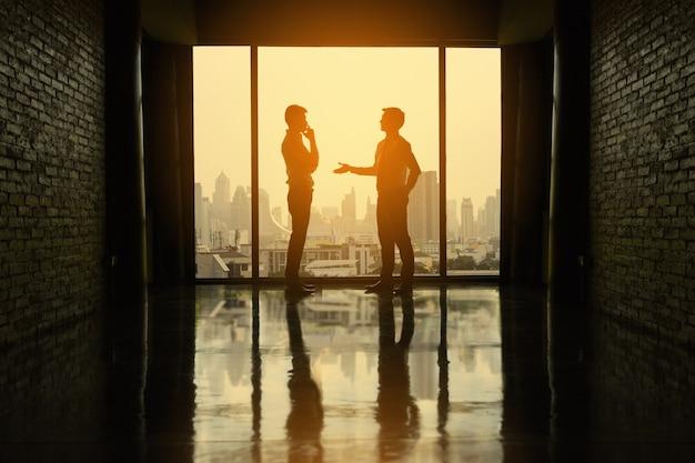 Twee zakenlieden onderhandelen zaken in bureau op het gebouw.