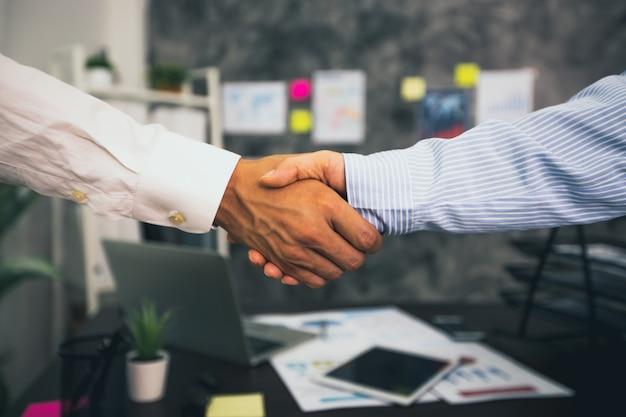 Twee zakenlieden schudden elkaar de hand op kantoor Premium Foto
