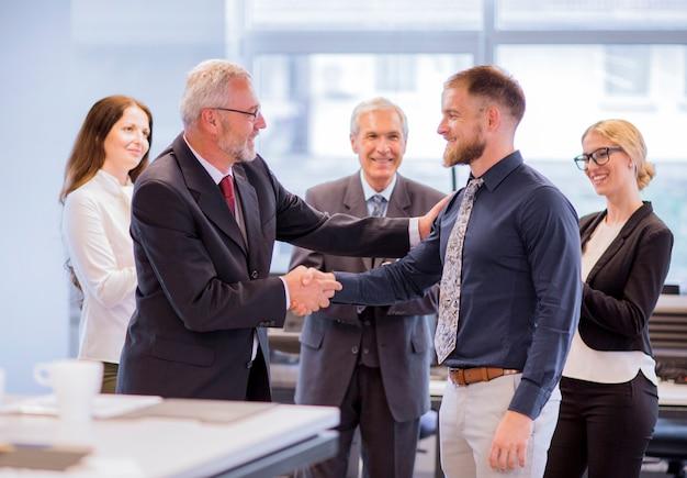 Twee zakenlieden schudden handen feliciteren met promotie