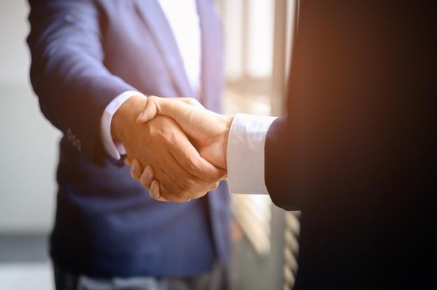 Twee zakenlieden slaan de handen ineen voor samenwerking tussen bedrijven.