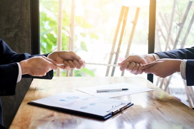 Twee zakenlieden spelen touwtrekken teams vechten om te winnen