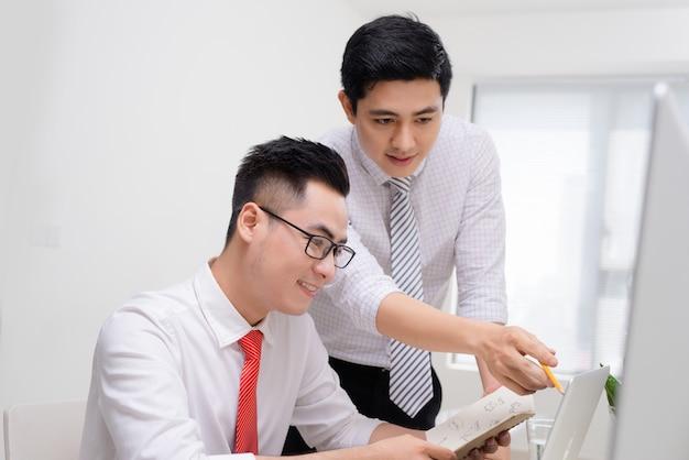 Twee zakenlieden werken samen met de computer op het bureau, een van hen wijst naar het scherm.