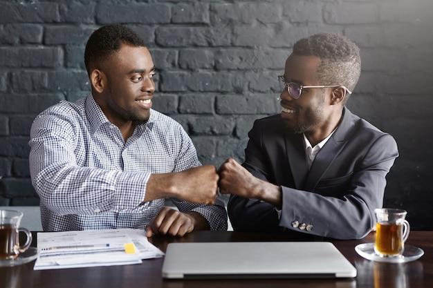 Twee zakenlui met een donkere huidskleur in formele kleding geven elkaar een vuist