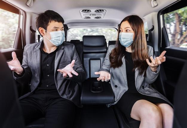 Twee zakenman en vrouw die gezichtsmasker dragen ter bescherming van covid-19 (coronavirus) en praten terwijl ze op de achterbank van een auto zitten