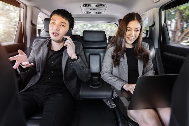 Twee zakenman en -vrouw die mobiele telefoons en laptops gebruiken terwijl ze op de achterbank van een auto zitten