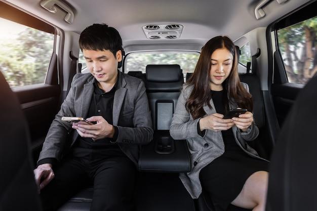 Twee zakenman en -vrouw die smartphone gebruiken terwijl ze op de achterbank van een auto zitten