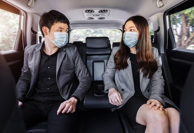 Twee zakenman en vrouw met gezichtsmasker ter bescherming van covid-19 (coronavirus) terwijl ze op de achterbank van een auto zitten