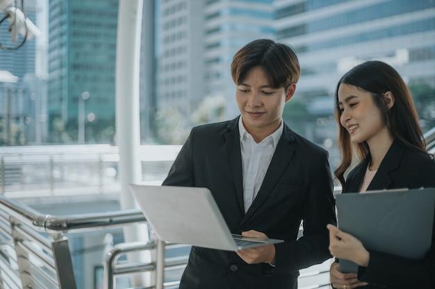 Twee zakenman en vrouwen staande vergadering met behulp van laptop voor project.