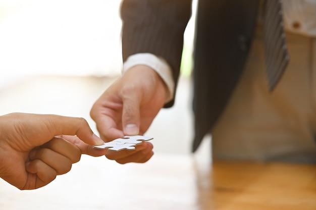 Twee zakenman hand verbinden puzzel.