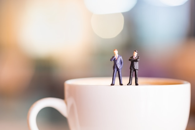 Twee zakenman miniatuurcijfers bevinden zich en denken op witte plaat van kop hete koffie.