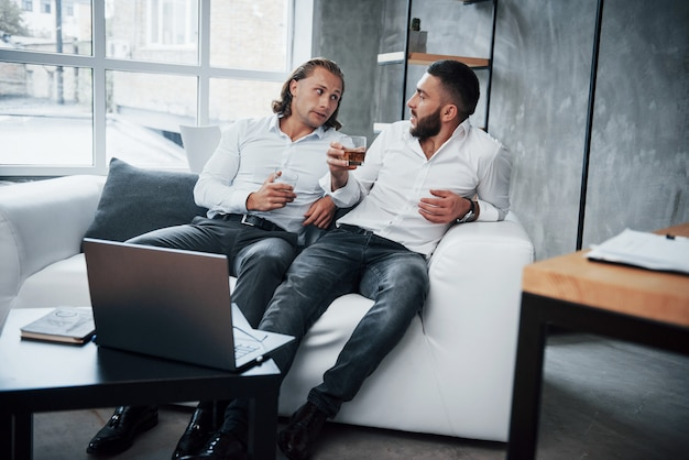 Twee zakenman zit achter laptop praten over hun plannen en het drinken van whisky