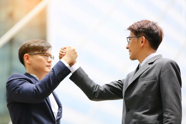 Twee zakenmanhanddrukken tegen de bouw