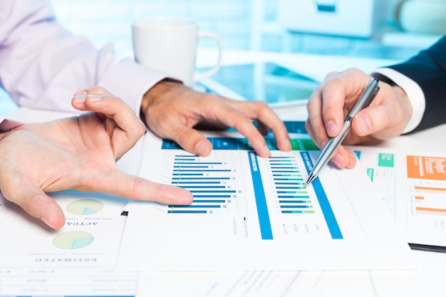 Twee zakenmanhanden die sommige businessplannen op vergadering bespreken