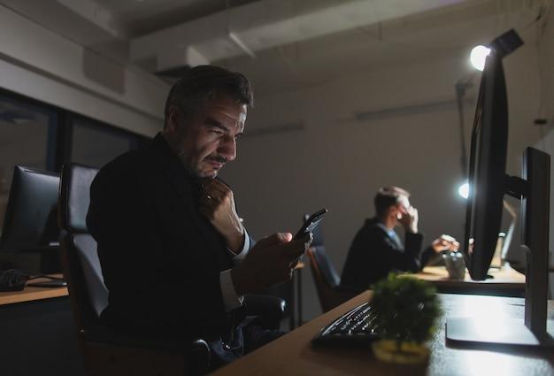 Twee zakenmannen voelen zich moe en uitgeput op kantoor
