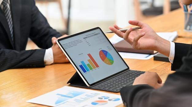 Twee zakenmanvergadering en overlegt met digitale draagbare computer op lijst.