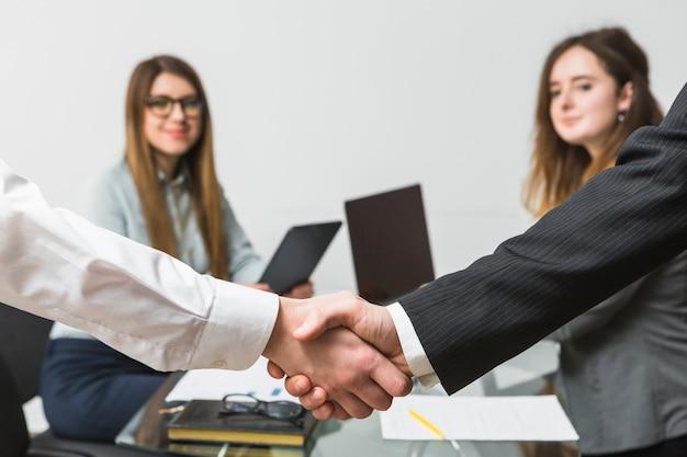 Twee zakenmensen handen schudden voor vrouwelijke uitvoerende macht op de werkplek