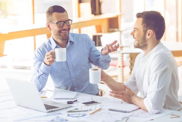 Twee zakenmensen in klassieke shirts drinken koffie.