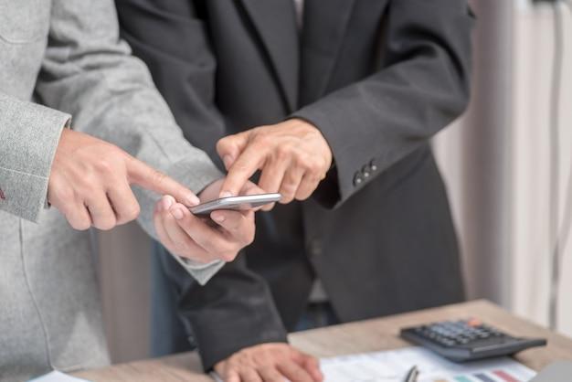 Twee zakenmensen kijken naar mobiel