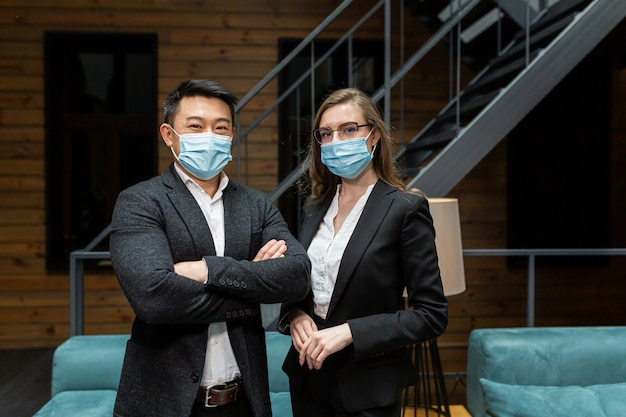 Twee zakenmensen met beschermende maskers kijken naar de camera zakenpartners man en vrouw in een zakelijke bijeenkomst