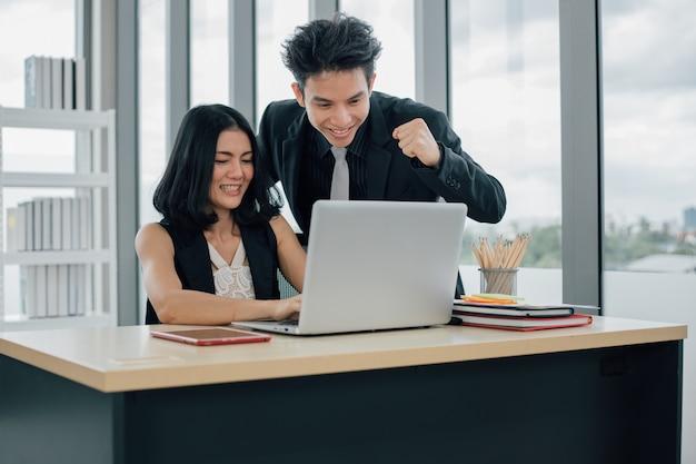 Twee zakenmensen werken samen met een glimlach op het gezicht met behulp van laptop op kantoor