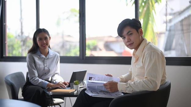 Twee zakenmensen zitten samen op kantoor en kijken naar de camera.