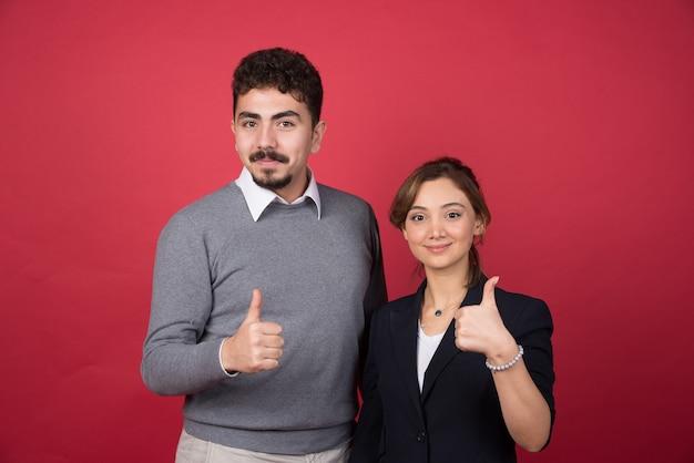 Twee zakenpartners die duimen op rode muur opgeven