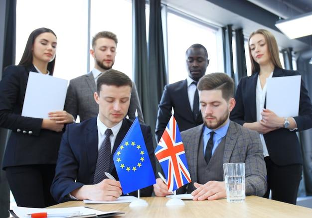 Twee zakenpartners die een document ondertekenen. de europese unie en groot-brittannië. brexit