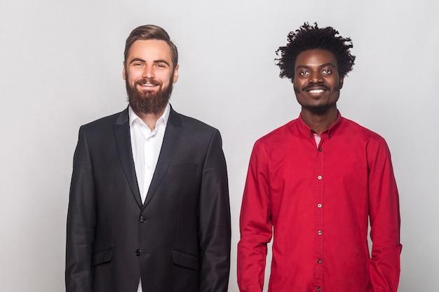 Twee zakenpartners, staande bij elkaar, kijkend naar camera en brede glimlach. studio opname, grijze achtergrond