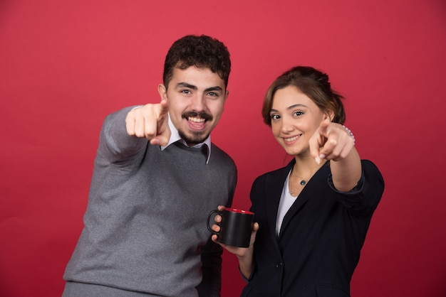 Twee zakenpartners wijzen naar voren op rode muur