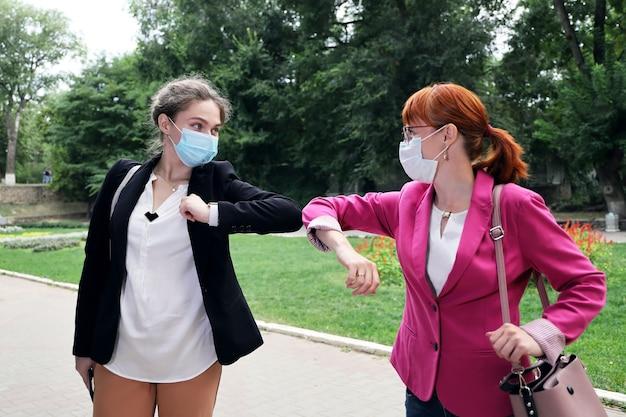 Twee zakenvrouw met gezichtsmasker tijdens de groet ellebogen