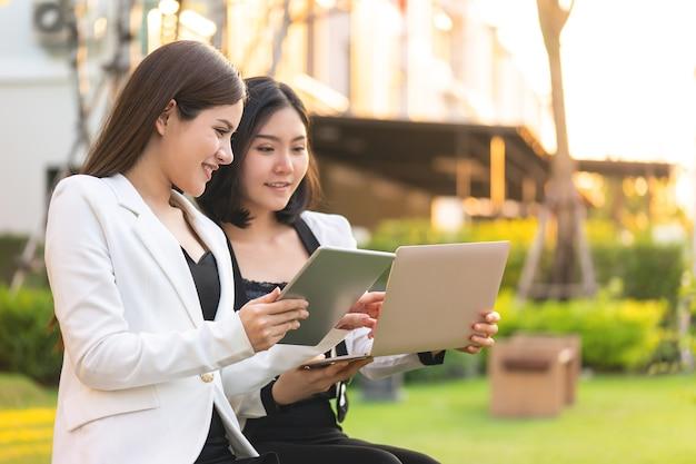 Twee zakenvrouw werkt samen in een park buiten