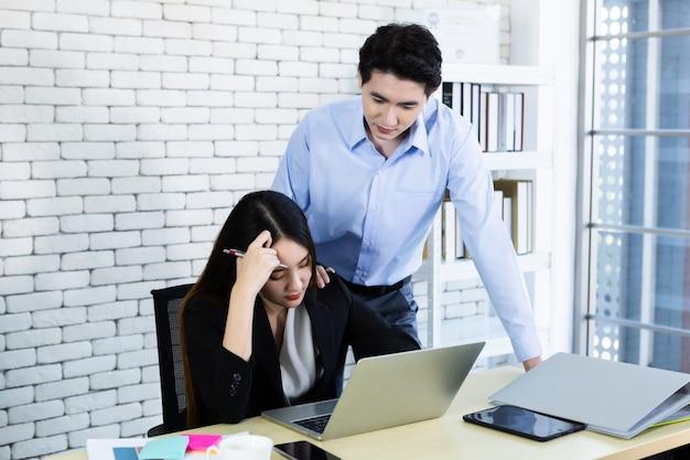 Twee zakenvrouw worden benadrukt op het werk met zaken man partners helpen bij het maken van positieve aanbevelingen werken met de computer op houten tafel en ideeën tijdens bijeenkomst op kantoor achtergrond.