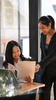 Twee zakenvrouwcollega's die ideeën over nieuwe bedrijfsstrategie delen op modern kantoor