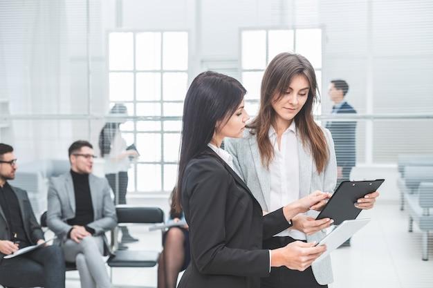 Twee zakenvrouwen bespreken zakelijke documenten op kantoor. bedrijfsconcept