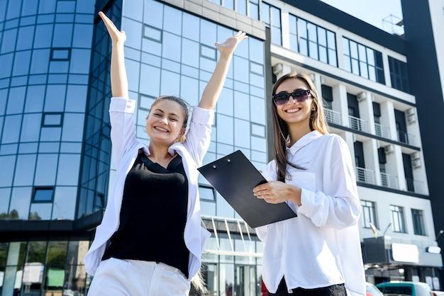 Twee zakenvrouwen die buiten staan