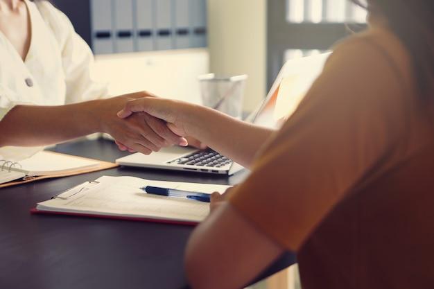 Twee zakenvrouwen die elkaar de hand schudden om de succesvolle zakelijke onderhandelingen te feliciteren, gaan goed.
