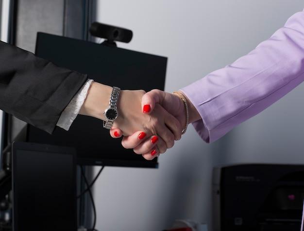 Twee zakenvrouwen gemanicuurde handen met rode nagellak handenschudden nadat de vrouwelijke deal is gedaan als concept van respect, succesvol teamwork, samenwerking en ondersteuning, vrouwenmacht in het bedrijfsleven