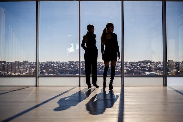 Twee zakenvrouwen genieten van het uitzicht op de stad en praten terwijl ze bij het grote raam op kantoor staan