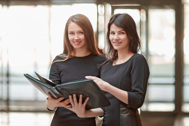 Twee zakenvrouwen lezen zakelijke documenten die in de kantoorlobby staan.