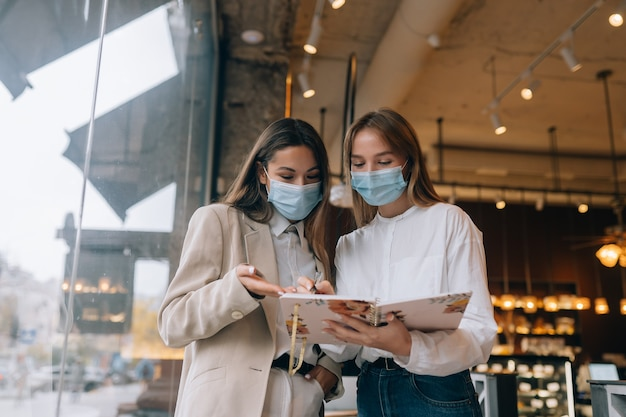 Twee zakenvrouwen met hun gezichtsmaskers discussiëren over verschillende opvattingen over werk