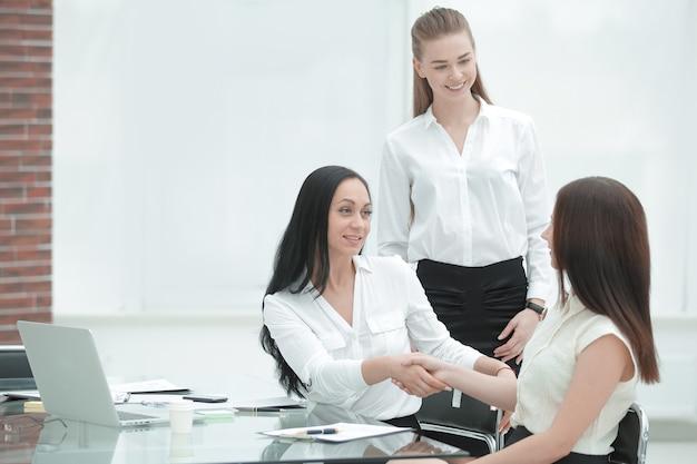 Twee zakenvrouwen schudden elkaar de hand boven het ondertekende contract.
