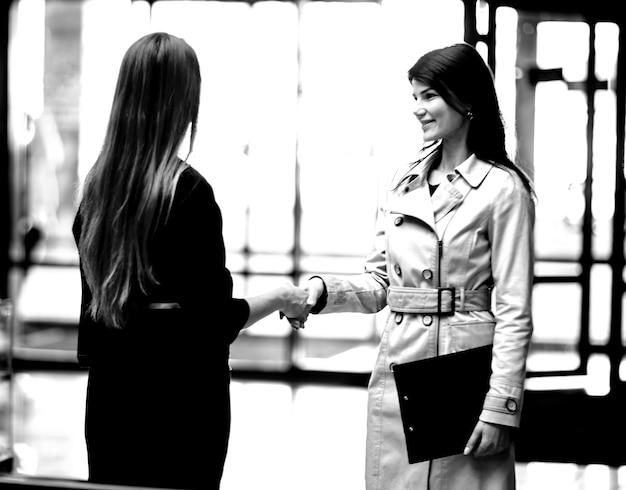 Twee zakenvrouwen schudden handen in de kantoorlobby.