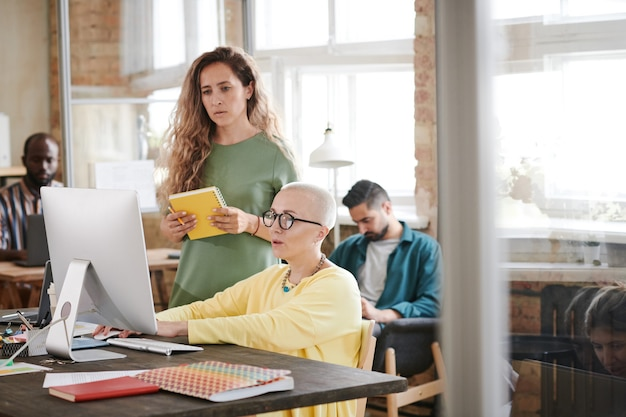 Twee zakenvrouwen werken samen aan een ontwerpproject op de computer op kantoor