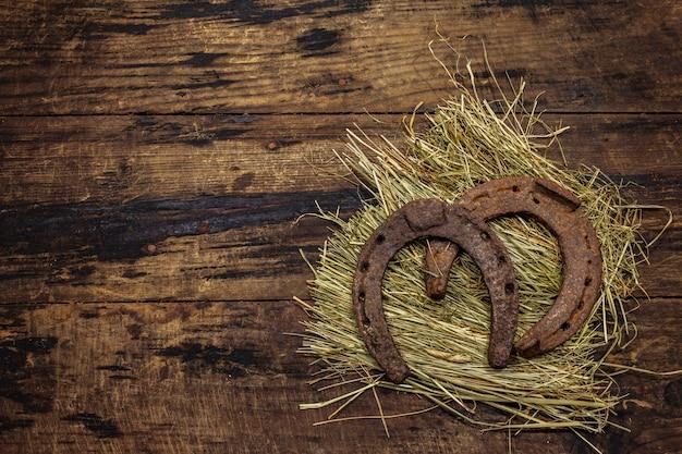 Twee zeer oude gietijzeren metalen paardenhoeven op hooi. veel geluk symbool, st.patrick's day concept. antieke houten achtergrond