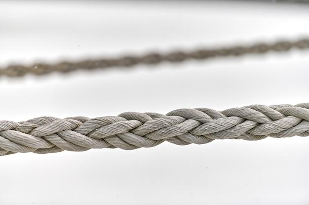 Twee zeilkabels die aan het vissersschip of jacht hangen, sluiten omhoog. gedetailleerd fragment van touw.