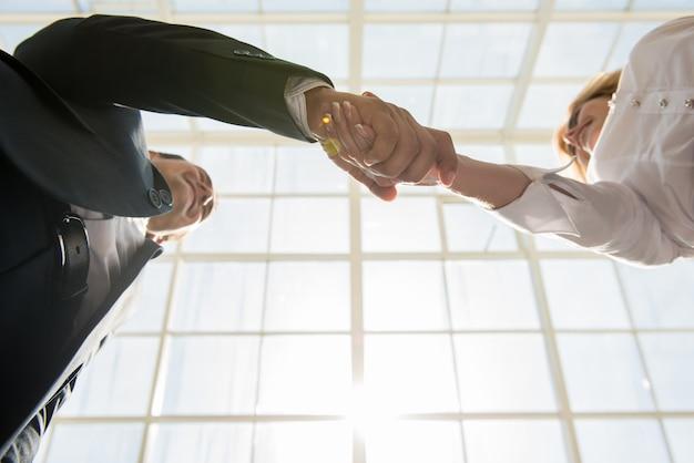 Twee zekere bedrijfsmensen die handen schudden op kantoor.