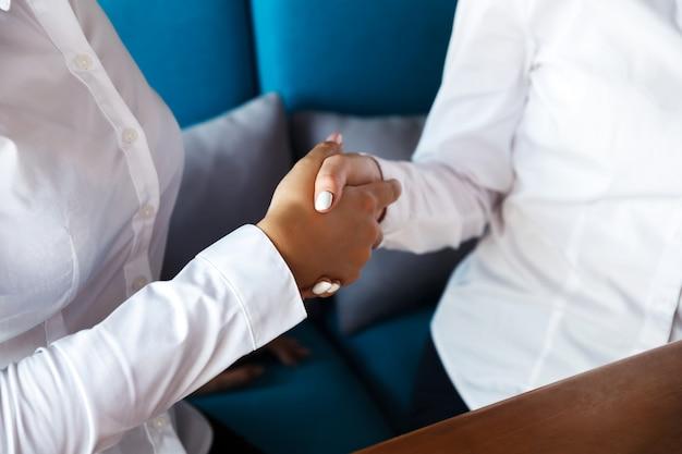 Twee zekere bedrijfsvrouwen die handen schudden tijdens een vergadering in het bureau