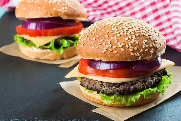 Twee zelfgemaakte cheeseburgers met runderpasteitjes en frisse salade op seasame-broodjes, geserveerd op zwarte leisteen.